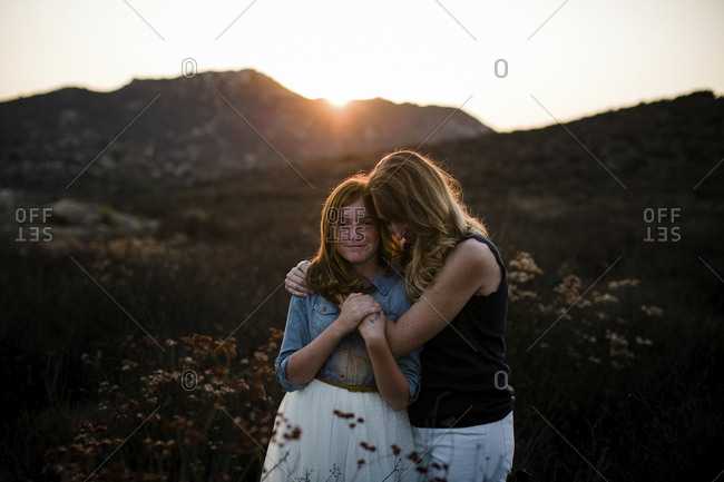 Mother embracing daughter while standing on field against mountains during sunset
