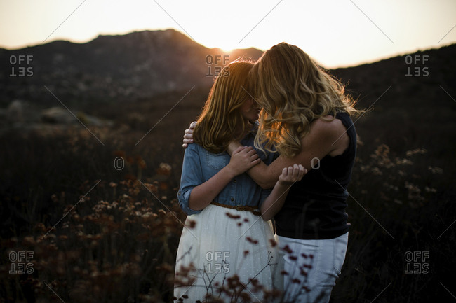 Mother and daughter embracing while standing on field against mountains during sunset