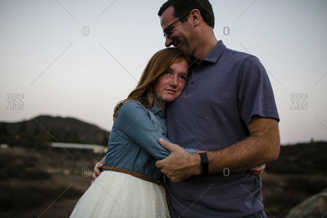 Daughter embracing father while standing on field against sky during sunset