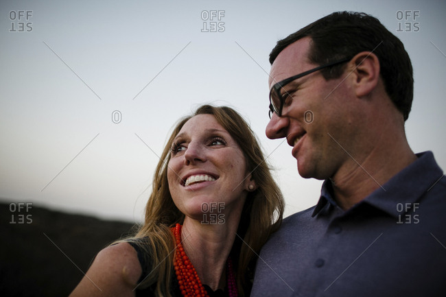 Close-up of happy couple against sky during sunset