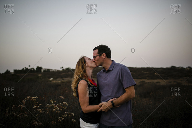 Loving couple kissing while standing on field against clear sky during sunset
