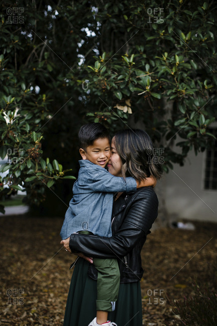 Smiling mother carrying cute son while standing against trees in Balboa Park