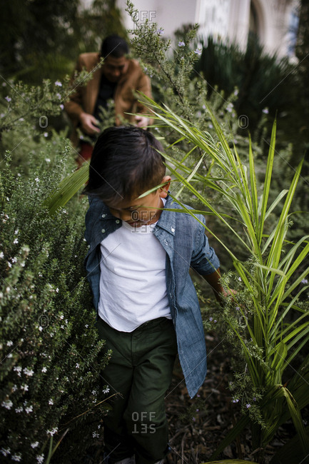 Close-up of son walking amidst plants against father in Balboa Park