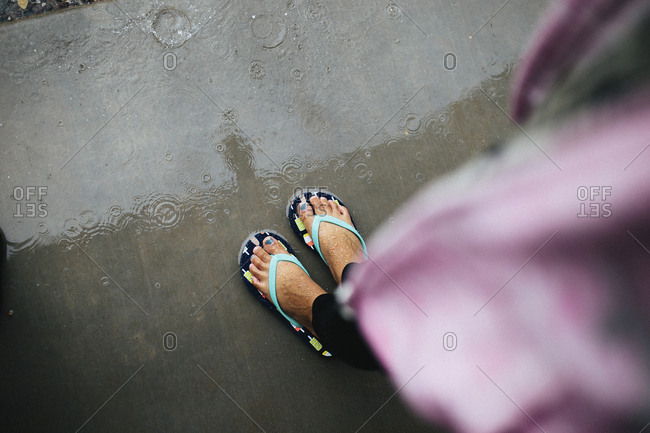 Low section of girl wearing flip-flops standing on wet street during rainfall