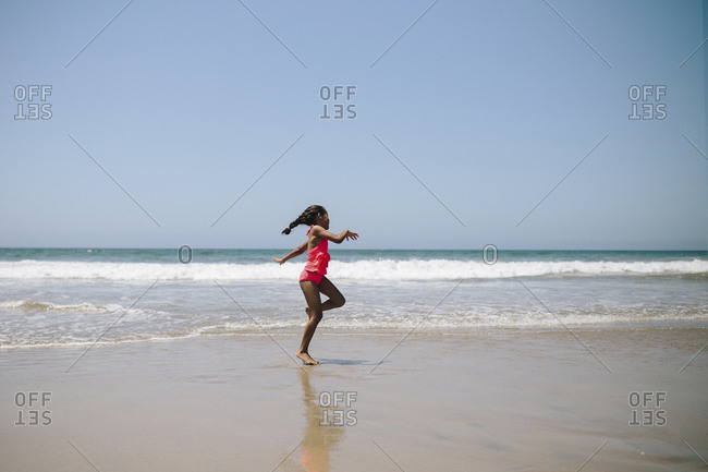 Girl in swimwear dancing at beach against clear sky during sunny day