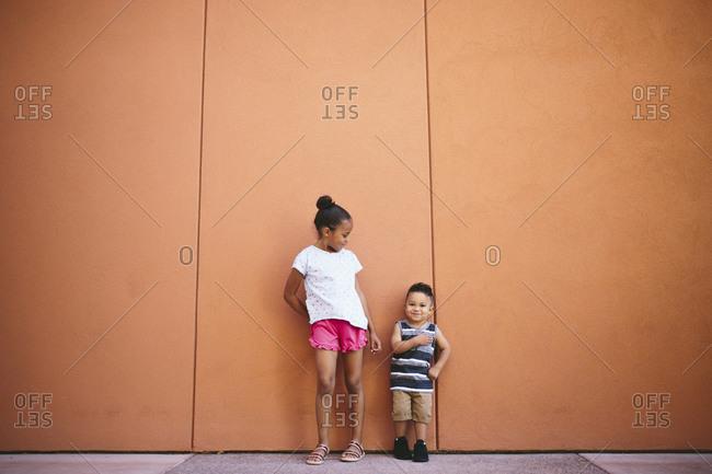 Full length of siblings standing on footpath against orange wall