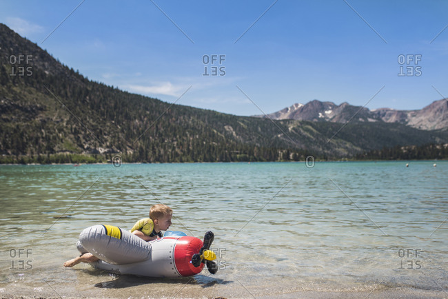 Cute playful boy lying on inflatable airplane by lake against mountains during summer