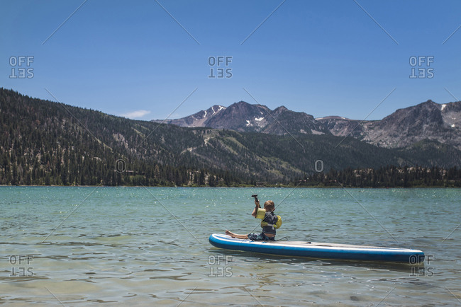 Full length of boy paddleboarding while sitting on paddleboard in lake against mountains and sky during sunny day