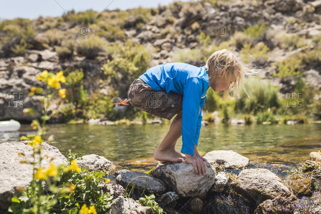 Side view of boy playing on rocks by lake during sunny day