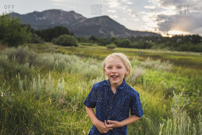Portrait of cheerful boy standing on grassy field against mountains during sunset