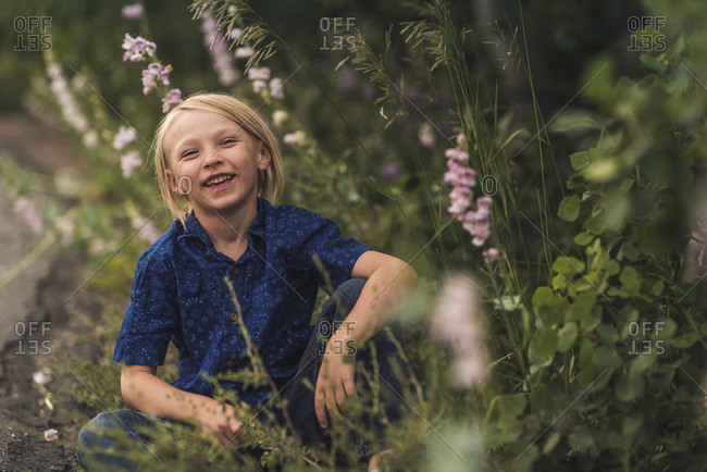 Portrait of carefree cheerful boy sitting by plants on field