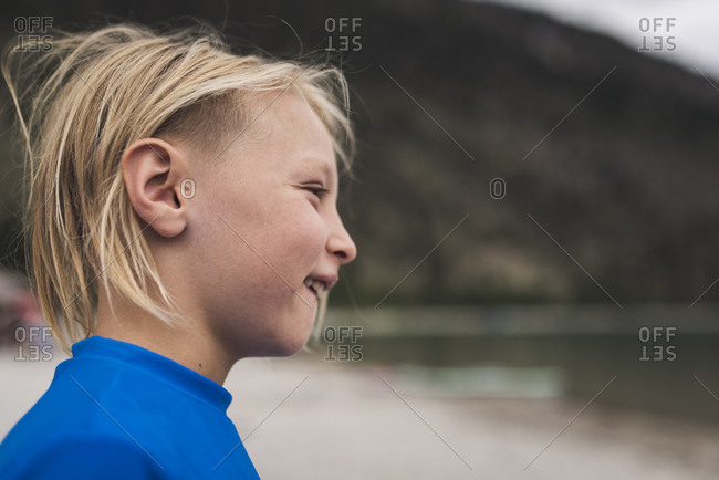 Side view of smiling boy looking away while standing against mountain