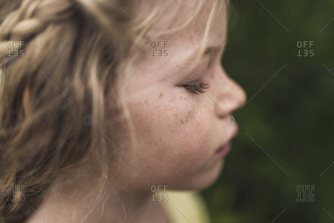 Side view close-up of girl with eyes closed standing in forest