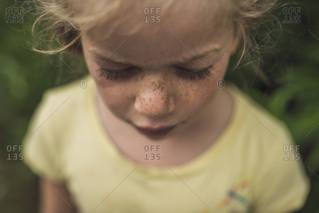 High angle close-up of girl with freckles standing in forest