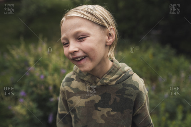 Close-up of happy boy with blond hair looking away while standing on grassy field in forest