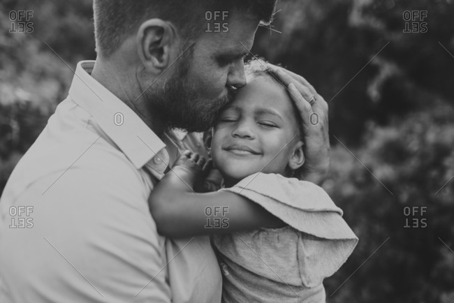 Close-up of father embracing cute daughter while standing in park