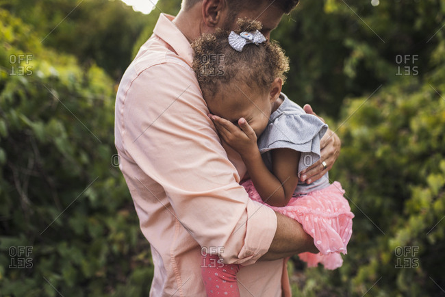 Side view of father embracing daughter while standing against plants in park