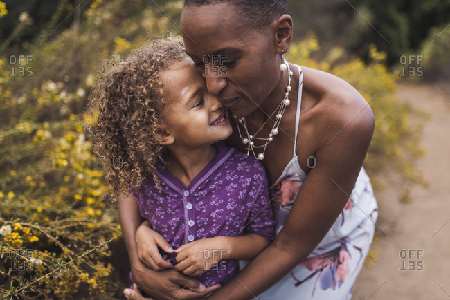 Mother embracing smiling daughter while standing against plants in park