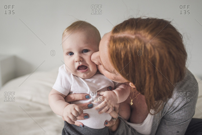 Close-up of mother kissing cute son while sitting on bed against wall at home