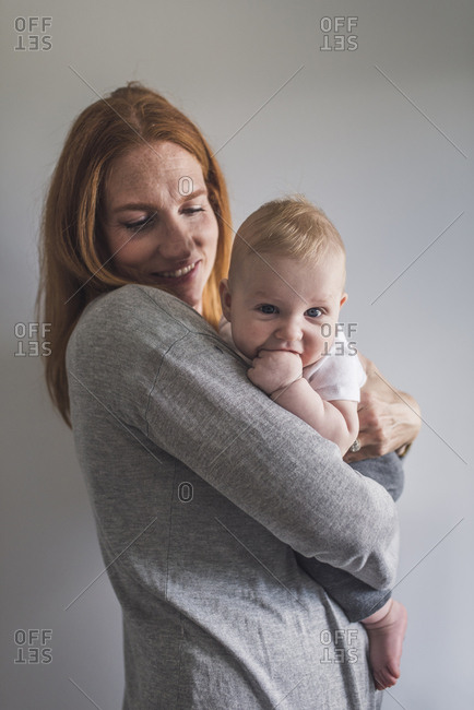 Smiling mother carrying cute son while standing against gray wall at home