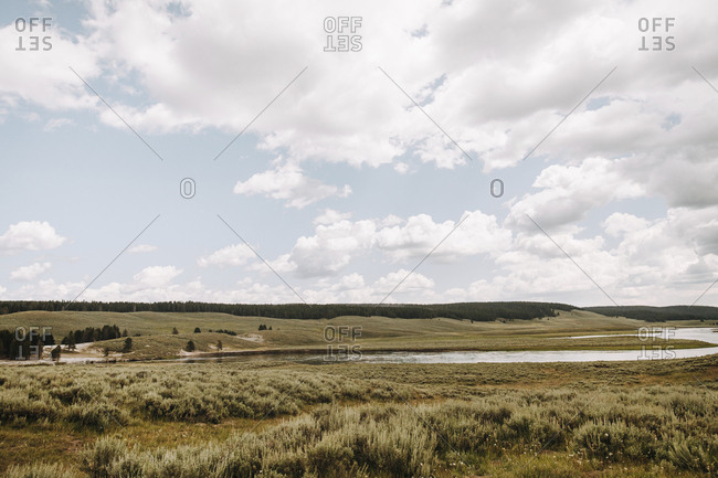 Scenic view of landscape against cloudy sky at Yellowstone National Park