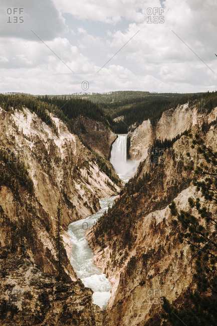 Scenic view Of Yellowstone Falls Against Cloudy Sky In forest