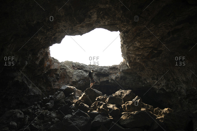 Low angle view of man standing on rock in cave against clear sky