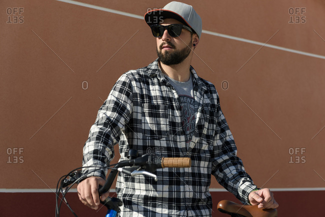 Confident man wearing sunglasses while standing with bicycle against building in city during sunny day