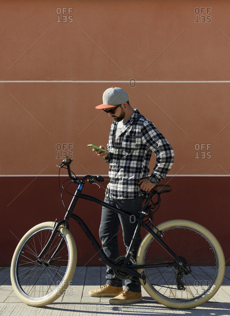 Man using smart phone while standing with bicycle on sidewalk against building during sunny day