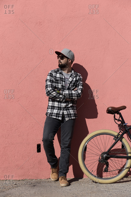 Confident man with arms crossed standing by bicycle on sidewalk against wall during sunny day