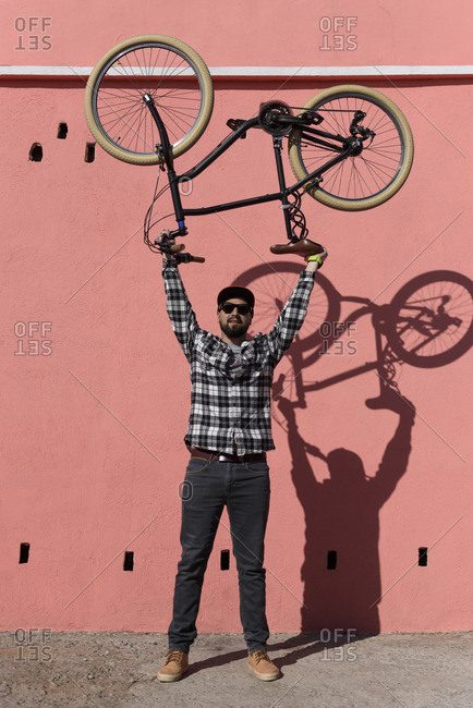Portrait of confident man carrying bicycle while standing on sidewalk against wall in city during sunny day