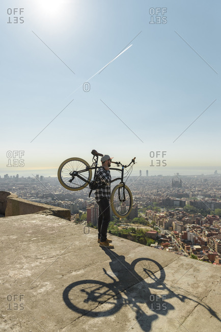 Side view of man carrying bicycle while standing on retaining wall over cityscape against sky during sunny day