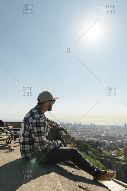 Side view of man looking at cityscape while sitting on retaining wall against sky during sunny day