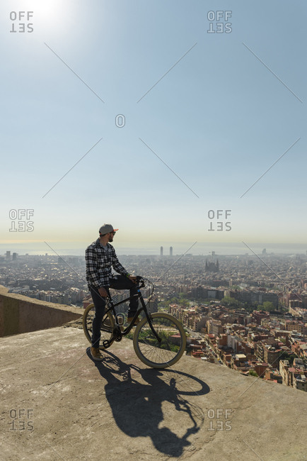 Side view of man looking at cityscape while sitting on bicycle against sky during sunny day