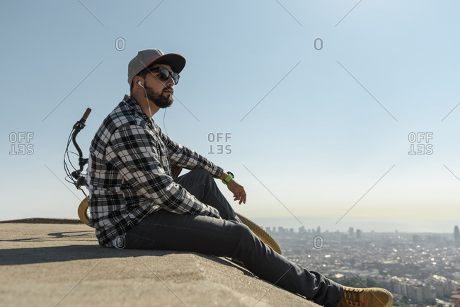 Side view of man wearing sunglasses listening music while sitting on retaining wall against clear blue sky during sunny day
