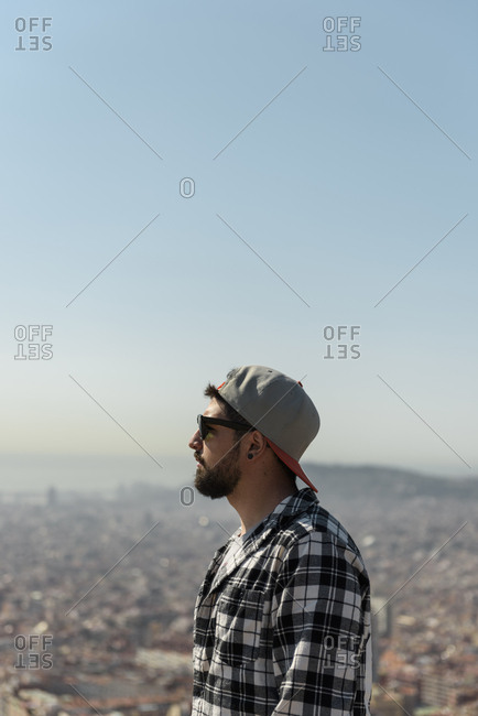 Side view of man wearing sunglasses looking at cityscape against clear blue sky during sunny day