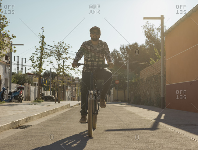 Confident man riding bicycle on street against clear sky during sunny day
