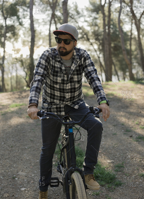 Man wearing sunglasses sitting on bicycle against trees in park during sunny day