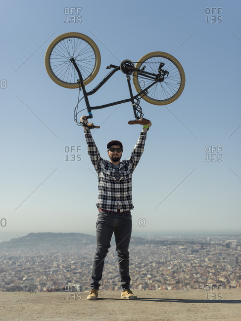 Portrait of confident man carrying bicycle while standing on retaining wall over cityscape against clear blue sky