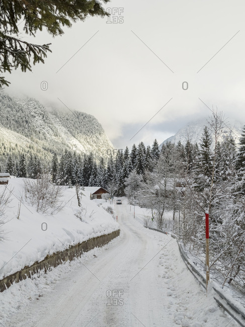 Snow covered road and trees against mountains and cloudy sky during winter