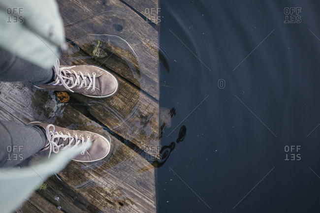 Low section of woman standing on pier over lake in forest