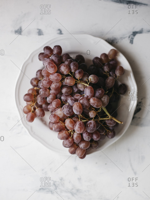 Overhead view of grapes in plate on marble table