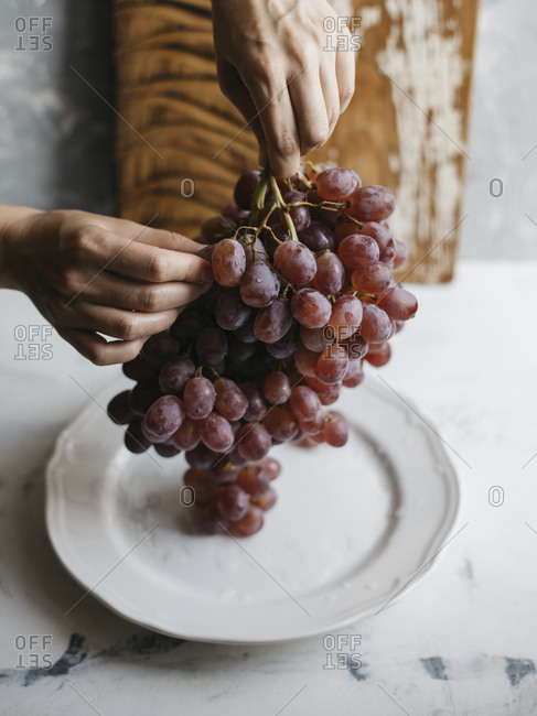 Cropped hands of woman holding grapes in plate on marble table at home
