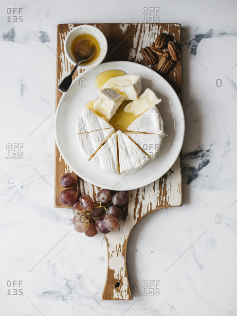 High angle view of cheese with grapes and pecan nuts served on wooden tray