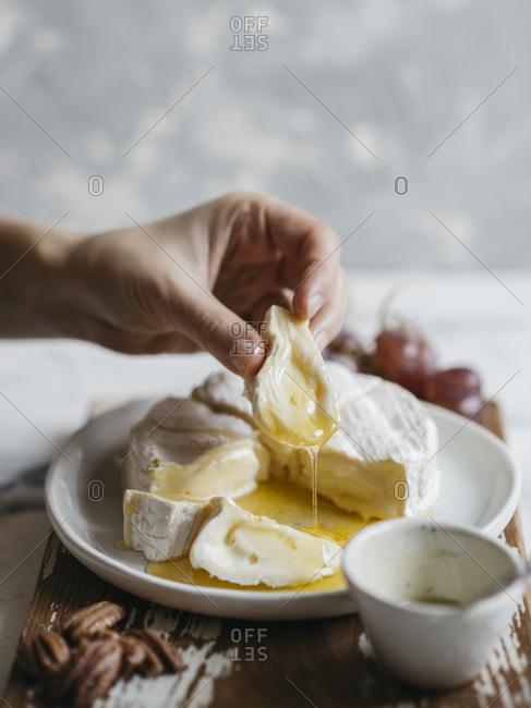 Cropped hand of woman eating breakfast served in plate on wooden tray against wall at home