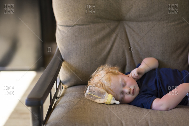 Cute baby boy sleeping by milk bottle on couch at home