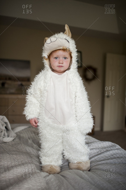Full length portrait of cute baby boy wearing animal costume standing on bed at home