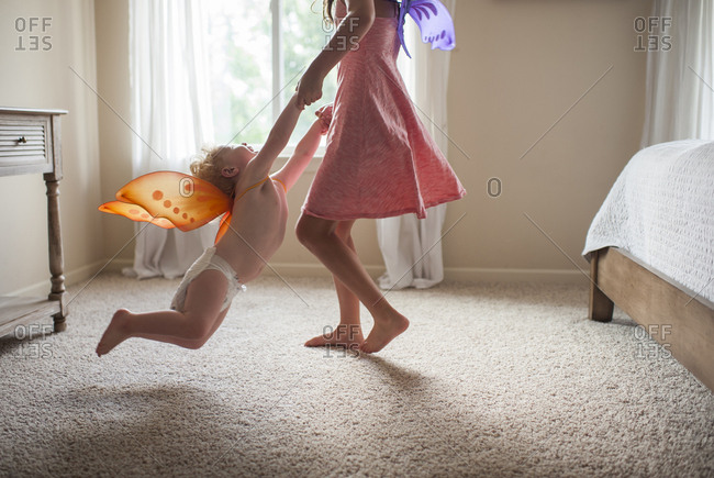 Low section of playful sister with costume wings holding brother's hands while spinning him in bedroom at home
