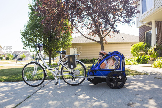 Brothers sitting in bike trailer on footpath