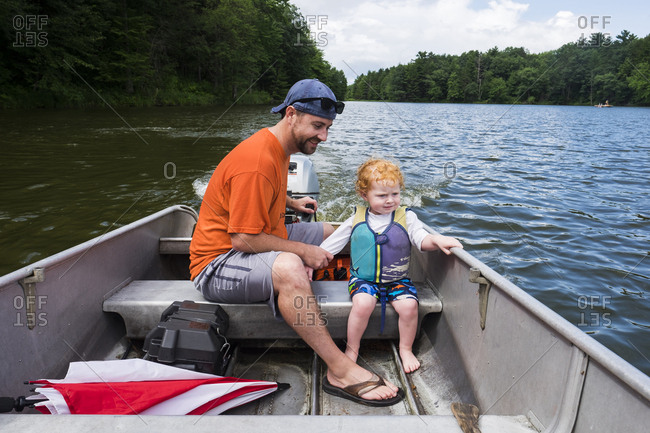 Full length of father and son sitting on motorboat in lake at forest